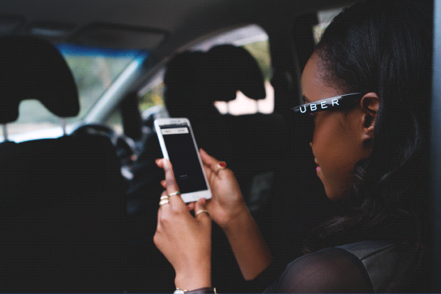 An Uber passenger in the rear seat of a car checking the status of her trip on her phone.